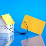 Paper house attached to yellow blank price tag on blue background